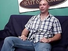 Hot bald gay stud plays with his dick on the couch